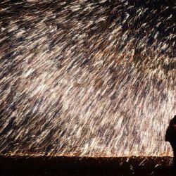 Esta foto muestra a un artista arrojando hierro fundido para crear fuegos artificiales durante una actuación tradicional china  | Foto:STR / AFP