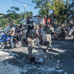 Los agentes de policía intentan despejar una carretera durante una manifestación en Port-au-Prince. - Varios miles de personas se manifestaron en la capital de Haití, Puerto Príncipe, diciendo que el gobierno estaba tratando de establecer una nueva dictadura y denunciando el apoyo internacional al presidente Jovenel Moise. | Foto:Reginald Louissaint Jr / AFP
