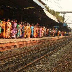 Pasajeros varados esperan su tren mientras estudiantes de izquierda junto con otros bloquean el servicio de ferrocarril suburbano para protestar contra las recientes reformas agrícolas del gobierno central, la brutalidad policial en Bengala Occidental y el aumento del precio de la gasolina, en Calcuta. | Foto:Dibyangshu Sarkar / AFP