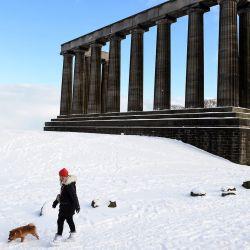 Una persona camina con un perro más allá del Monumento Nacional en Calton Hill, cubierto de nieve en el centro de Edimburgo. - El clima frío que azota el norte de Europa trae nieve y hielo. | Foto:Andy Buchanan / AFP