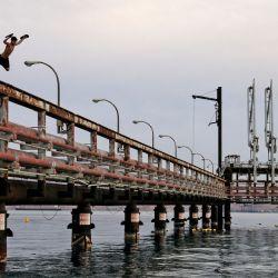 Los jóvenes saltan al agua del Mar Rojo desde un muelle petrolero abandonado en la ciudad portuaria de Eilat, en el sur de Israel. | Foto:Menahem Kahana / AFP)
