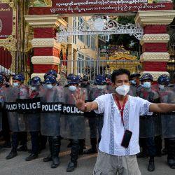 Un hombre hace un gesto hacia los residentes (invisible) mientras la policía monta guardia en la puerta de entrada de un monasterio budista donde se refugiaron simpatizantes pro-militares después de los enfrentamientos con los residentes locales luego de una manifestación contra el golpe militar en Yangon. | Foto:Ye Aung Thu / AFP