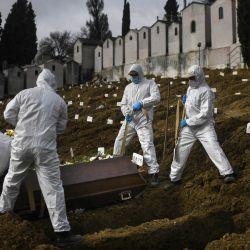Los excavadores de tumbas con trajes protectores entierran a una víctima de Covid-19 en el cementerio Alto de Sao Joao en Lisboa. | Foto:Patricia De Melo Moreira / AFP