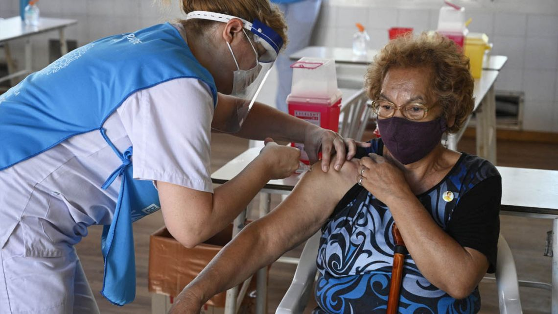 An elderly woman walks accompanied by a health worker after receiving a dose of the Sputnik V vaccine against Covid-19, in a temporary vaccination centre at a public school in Ezeiza, on the outskirts of Buenos Aires.