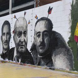 El artista callejero español RocBlackBlock trabaja en su nueva pintura mural que representa los retratos del rey Felipe VI de España (L), su padre, el ex rey Juan Carlos (C) y el dictador español Francisco Franco, en Barcelona. AFP | Foto:AFP