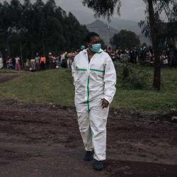 Un personal médico del hospital de Kivu del Norte se encuentra en una carretera mientras un residente local asiste en el borde del Parque Nacional Virunga cerca del pueblo de Kibumba, a unos 25 km de Goma, donde el embajador de Italia en la República Democrática del Congo, su guardaespaldas y conductor, murieron antes cuando su automóvil fue disparado mientras él estaba en una excursión. AFP | Foto:AFP