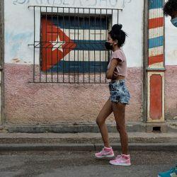 Jóvenes con mascarillas como medida de precaución contra la propagación del nuevo coronavirus, COVID-19, caminan en La Habana. AFP | Foto:AFP