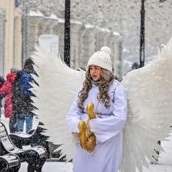 Una mujer vestida como un ángel, camina bajo la nieve en una calle del centro de Moscú. AFP | Foto:AFP
