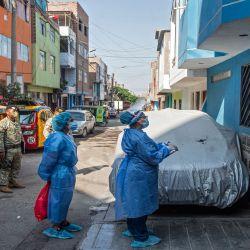 Trabajadores del Ministerio de Salud conversan con un residente en el distrito de Ate, en la periferia oriental de Lima, donde se revisa a los residentes y se les realizan pruebas para descartar COVID-19 hechas puerta a puerta. | Foto:AFP