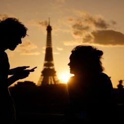 Una pareja, uno de ellos revisando su Smartphone, disfrutan de la vista de la Torre Eiffel al atardecer en París.  | Foto:AFP