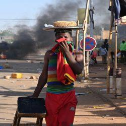Un hombre se tapa la boca mientras pasa junto a un incendio mientras los partidarios de la oposición de Níger protestan en una calle después del anuncio de los resultados de la segunda vuelta presidencial del país en Niamey Nigeria. | Foto:AFP