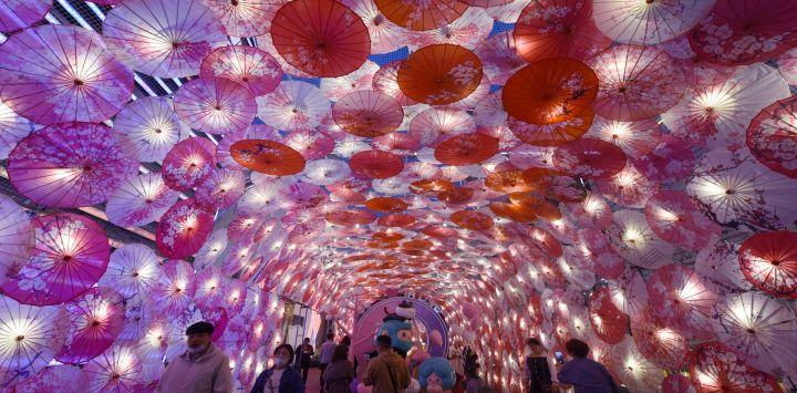 Muestra a personas que pasan junto a una exhibición de paraguas decorados con luces para el próximo Festival de los Faroles en una calle comercial en Hangzhou, en la provincia de Zhejiang, en el este de China.