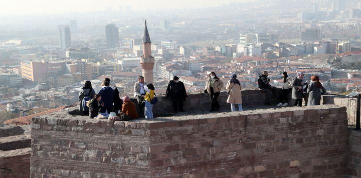 La gente disfruta de la vista de la ciudad mientras visita el Castillo de Ankara (Ankara Kalesi) en Ankara. Algunos de los edificios del Castillo de Ankara datan del siglo VII.