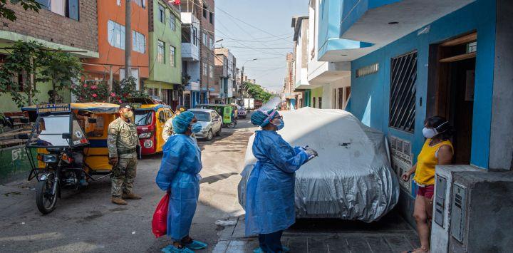 Trabajadores del Ministerio de Salud conversan con un residente en el distrito de Ate, en la periferia oriental de Lima, donde se revisa a los residentes y se les realizan pruebas para descartar COVID-19 hechas puerta a puerta.