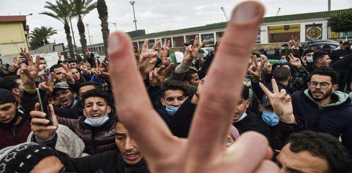 """Los policías son vistos al margen mientras los estudiantes corean consignas mientras se manifiestan en el centro de la capital de Argelia, Argel, un día después del segundo aniversario del movimiento de protesta """"Hirak""""."""
