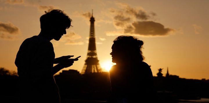 Una pareja, uno de ellos revisando su Smartphone, disfrutan de la vista de la Torre Eiffel al atardecer en París.