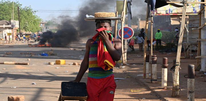Un hombre se tapa la boca mientras pasa junto a un incendio mientras los partidarios de la oposición de Níger protestan en una calle después del anuncio de los resultados de la segunda vuelta presidencial del país en Niamey Nigeria.