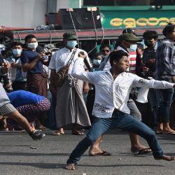 Los partidarios pro-militares lanzan proyectiles a los residentes en Yangon, luego de semanas de manifestaciones masivas contra el golpe militar. | Foto:AFP