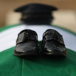 Los zapatos de un oficial de la Fuerza Aérea fallecida se ven en un ataúd envuelto con la bandera verde y blanca de la nación durante la ceremonia fúnebre de los siete miembros del personal militar, que murieron en el accidente de su avión, en el Cementerio Militar Nacional en Abuja. | Foto:AFP