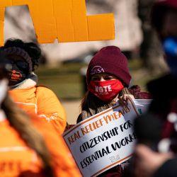 Una mujer sostiene un cartel mientras escucha a un orador durante una manifestación en apoyo del alivio de COVID-19, organizada por Shutdown DC, en el NationalMall, Washington DC. | Foto:AFP