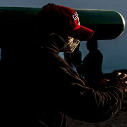 Un hombre carga un tanque de oxígeno vacío cuando llega a la cola para recargarlo en Villa El Salvador, en las afueras del sur de Lima. Familiares de pacientes con COVID-19 están desesperados por oxígeno para mantener con vida a sus seres queridos durante una feroz segunda ola de la pandemia en Perú. | Foto:AFP