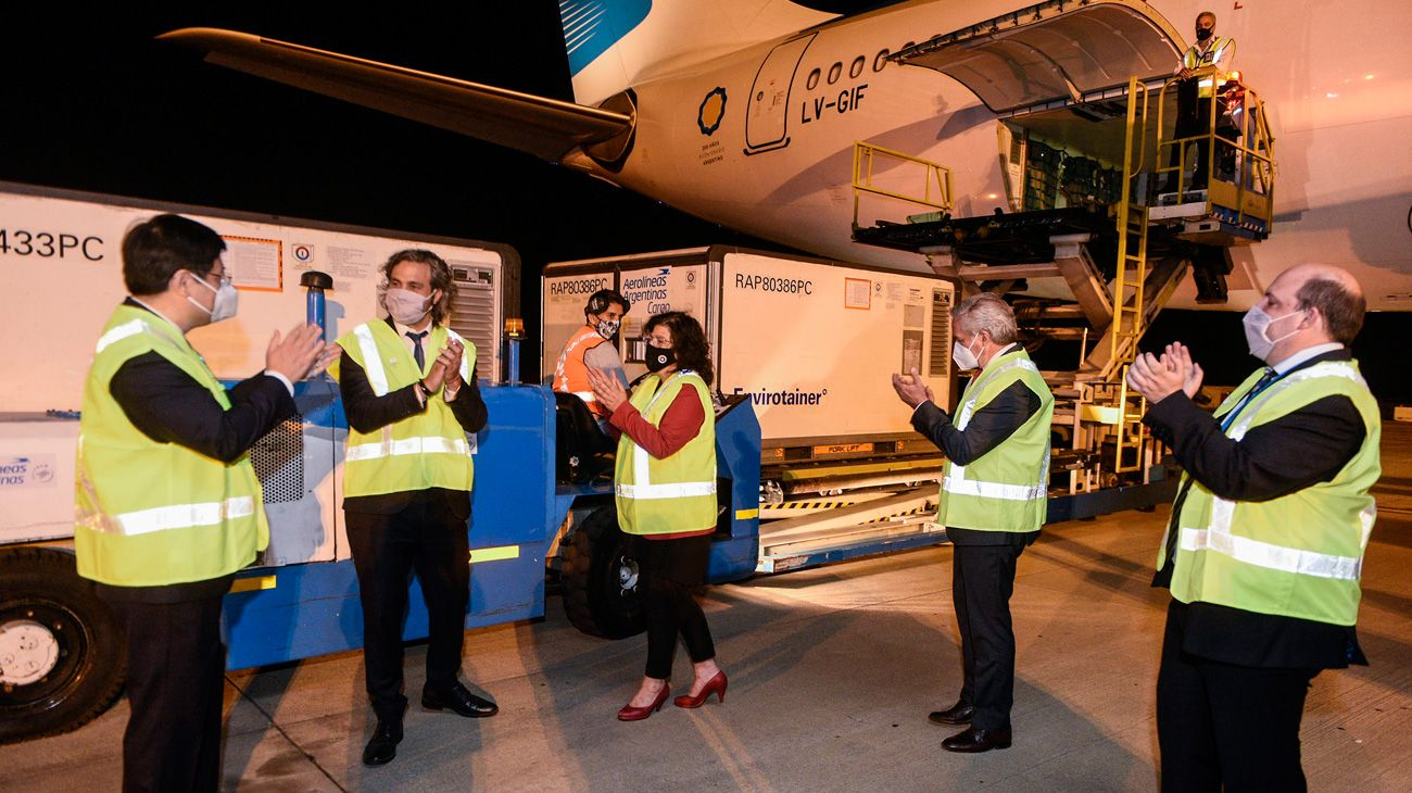 Officials applaud after the arrival of an Aerolíneas Argentinas plane carrying more than 900,000 doses of the Chinese laboratory Sinopharm's coronavirus vaccine, at Ezeiza international airport.