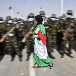 Una mujer envuelta en una bandera saharaui pasa junto a soldados vestidos con máscaras que se encuentran en formación durante las celebraciones del 45 aniversario de la declaración de la República Árabe Saharaui Democrática (SDAR), cerca de la ciudad de Tindouf, en el suroeste de Argelia, el 27 de febrero de 2021. | Foto:AFP