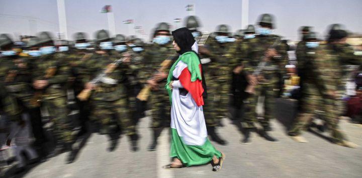 Una mujer envuelta en una bandera saharaui pasa junto a soldados vestidos con máscaras que se encuentran en formación durante las celebraciones del 45 aniversario de la declaración de la República Árabe Saharaui Democrática (SDAR), cerca de la ciudad de Tindouf, en el suroeste de Argelia, el 27 de febrero de 2021.