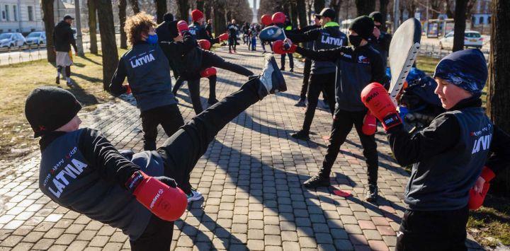 Los niños realizan ejercicios de karate mientras participan en un entrenamiento al aire libre como forma de protesta contra las restricciones del coronavirus (Covid-19) para recordar al gobierno que las actividades deportivas son muy importantes para la salud física y psicoemocional durante este período, en una plaza cercana el edificio del gobierno, en Riga el 27 de febrero de 2021. Debido a la pandemia, actualmente no se permite la apertura de gimnasios en Letonia.