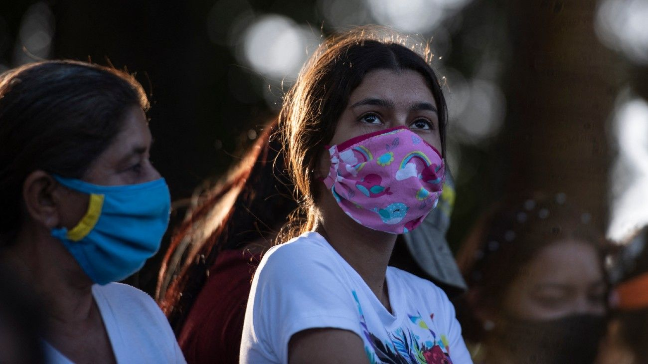 A girl along with other people participates in a religious event in memory of two young women murdered days ago in the town of La Mision in the state of Portuguesa, Venezuela on February 27, 2021.