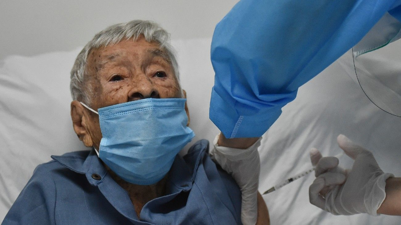 Dalia Patino, 103, is inoculated with a vaccine against Covid-19, at the San Miguel nursing home in Cali, Colombia, on February 25, 2021. Luis ROBAYO / AFP