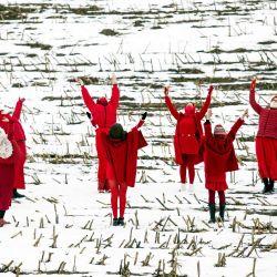 Mujeres vestidas de rojo bailan sosteniendo tulipanes rojos mientras dan la bienvenida a la primavera meteorológica durante una protesta contra los resultados de las elecciones presidenciales de Bielorrusia cerca de la aldea de MalojeZapruddzie. | Foto:AFP