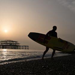 Un surfista lleva su tabla mientras sale del mar cerca del West Pier mientras el sol se pone sobre Brighton, East Sussex. | Foto:AFP
