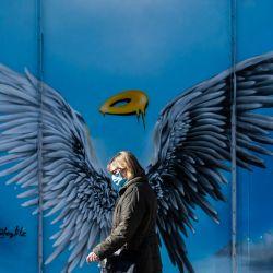Una mujer con una máscara facial pasa junto a una pintura mural con alas de ángel y un halo, en un centro comercial en el suroeste de Berlín.  | Foto:AFP