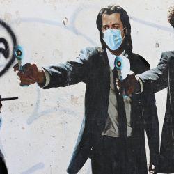 Un hombre pasa junto a un mural que muestra a los actores estadounidenses John Travolta y Samuel L. Jackson sosteniendo termómetros en lugar de armas en medio de la pandemia de Covid-19.  | Foto:AFP