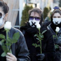Mujeres vestidas con ropa negra y cinta adhesiva cruzada sobre la boca sostienen rosas blancas mientras marchan, en Minsk, durante una manifestación contra la condena de un médico y un periodista por la divulgación de los registros médicos de un manifestante que murió después de ser detenido. | Foto:AFP