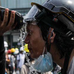 Un manifestante se pone agua en la cara después de que la policía lanzara gases lacrimógenos durante una manifestación contra el golpe militar en Yangon.  | Foto:AFP