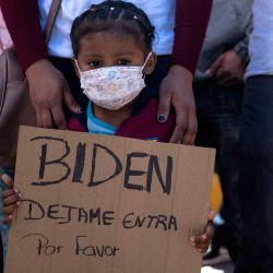 Dareli Matamoros, una niña de Honduras, sostiene un cartel pidiendo al presidente Biden que la deje entrar durante una manifestación de migrantes exigiendo políticas migratorias más claras de Estados Unidos, en el puerto de cruce de San Ysidro en Tijuana, estado de Baja California, México.  | Foto:AFP