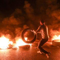 Un manifestante incendia un neumático mientras corta una carretera en el centro de la capital del Líbano, Beirut. Durante una protesta contra el deterioro de las condiciones económicas y sociales. | Foto:AFP