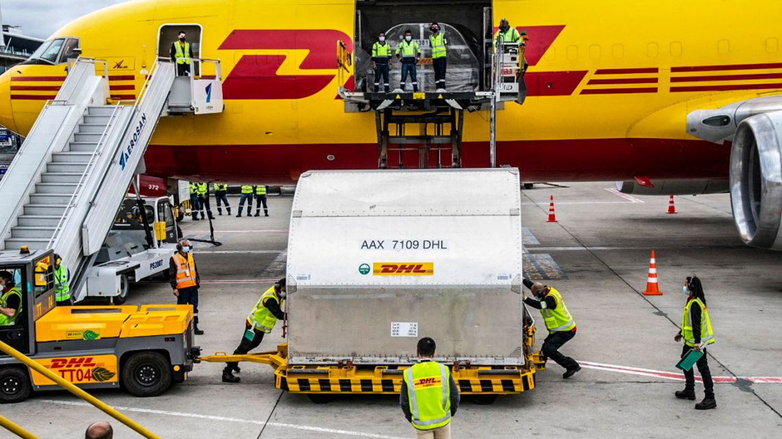 Handout picture released by the Colombian Presidency shows airport workers unloading 117,000 doses of vaccines against Covid-19 delivered through the Covax mechanism, at El Dorado airport international in Bogota on March 1, 2021.