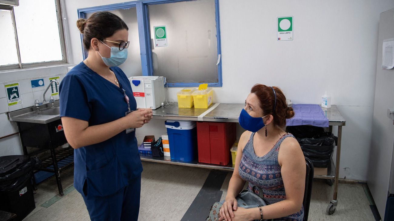 Chilean nurse Maria Paz Herreros, 32, who was the first to inoculate a patient against Covid-19 in Chile, speaks with a patient about the Chinese Sinovac vaccine, at the Metropolitan Hospital in Santiago, on February 26, 2021.