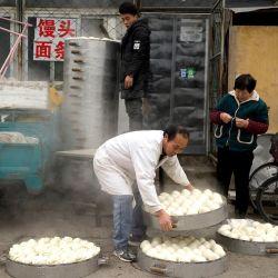Los trabajadores preparan bollos al vapor a lo largo de una calle en Beijing. | Foto:AFP