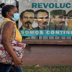 Una mujer con mascarilla como medida de precaución contra la propagación del COVID-19, camina junto a una pancarta con imágenes de líderes de la Revolución Cubana y del presidente Miguel Díaz-Canel (izq.), En La Habana. | Foto:AFP