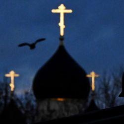 Un pájaro vuela delante de una iglesia al atardecer en las afueras de Moscú.  | Foto:AFP