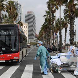El personal médico del Hospital del Mar lleva a la paciente del COVID-19, Marta Pascual, de 72 años, de vuelta al hospital tras tomar un poco de aire fresco junto al mar, en la explanada de la playa de la Barceloneta.   Foto:AFP