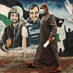 Un palestino con una máscara facial pasa junto a un mural de periodistas asesinados en el 2014 entre Hamas e Israel, en la ciudad de Gaza.    Foto:AFP