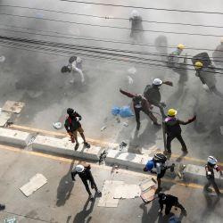Los manifestantes reaccionan después de que las fuerzas de seguridad dispararan gas lacrimógeno en un intento de dispersarlos durante una manifestación contra el golpe militar en Yangon.   Foto:AFP