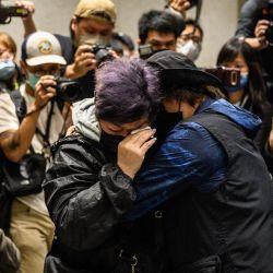 Los partidarios se consuelan entre sí mientras están rodeados por miembros de los medios de comunicación fuera del Tribunal de West Kowloon en Hong Kong, al final de una audiencia maratónica de libertad bajo fianza.    Foto:AFP