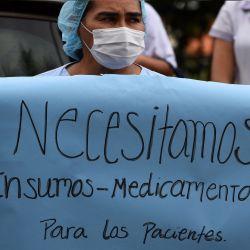 Una trabajadora de salud sostiene un cartel mientras participa en una protesta contra la corrupción y para denunciar la falta de medicamentos y recursos para combatir la enfermedad COVID-19, en el Hospital Clínicas de San Lorenzo, Paraguay.    Foto:AFP