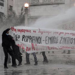 Los manifestantes intentan sostener una pancarta bajo el agua rociada por la policía antidisturbios en el centro de Atenas.    Foto:AFP